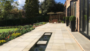 Elegant terrace and water feature in contemporary new build garden design in Harpenden by Amanda Broughton