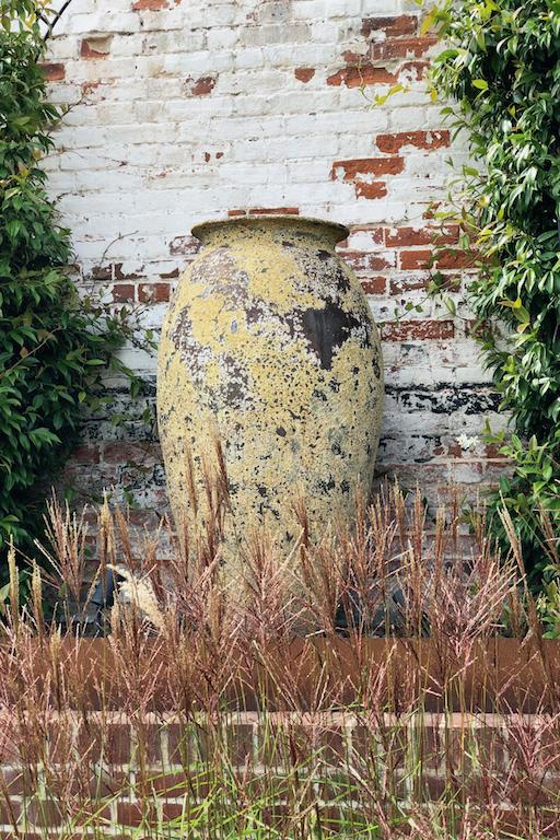 Antique effect urn framed with planting