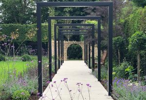 Contrasting original and contemporary arches in Herts. garden design